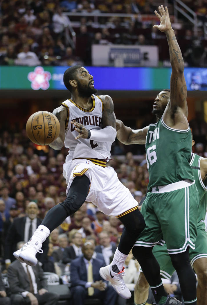 Cleveland Cavaliers' Kyrie Irving (2) passes around Boston Celtics' Marcus Smart (36) during the second half of Game 4 of the NBA basketball Eastern Conference finals, Tuesday, May 23, 2017, in Cl ...