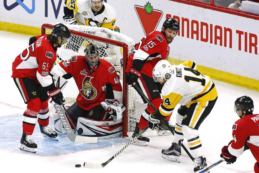Pittsburgh Penguins left wing Chris Kunitz (14) shoots on Ottawa Senators goalie Craig Anderson (41) as Senators defenseman Erik Karlsson (65) and Senators centre Zack Smith (15) defend during the ...