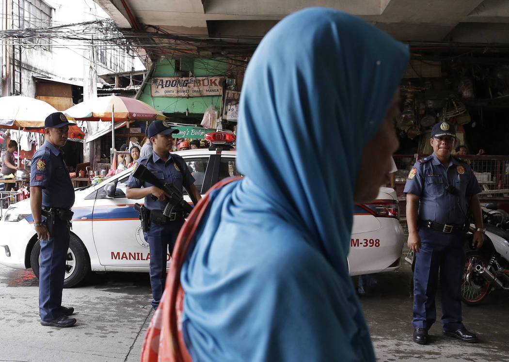 A Muslim woman passes by policemen at a checkpoint in downtown Manila, Philippines, Wednesday, May 24, 2017 as the Philippine National Police is placed under full alert status following the declar ...