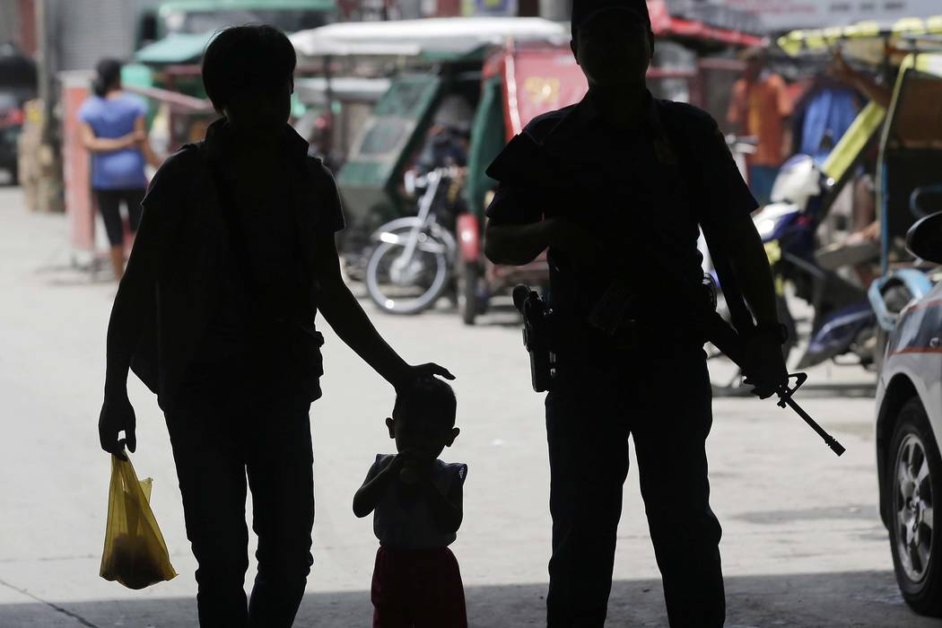 A policeman stands at a checkpoint in Manila, Philippines, Wednesday, May 24, 2017, as the Philippine National Police is placed under full alert status following the declaration of martial law in  ...
