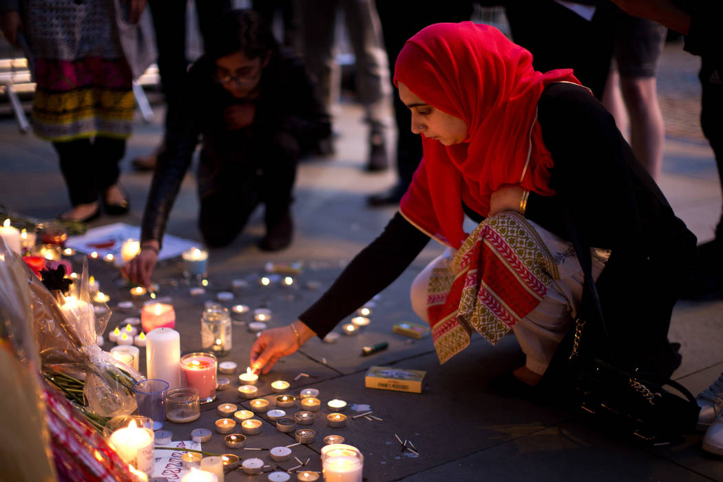 A woman lights candles after a vigil in Albert Square, Manchester, England, Tuesday May 23, 2017, the day after the suicide attack at an Ariana Grande concert that left 22 people dead as it ended  ...