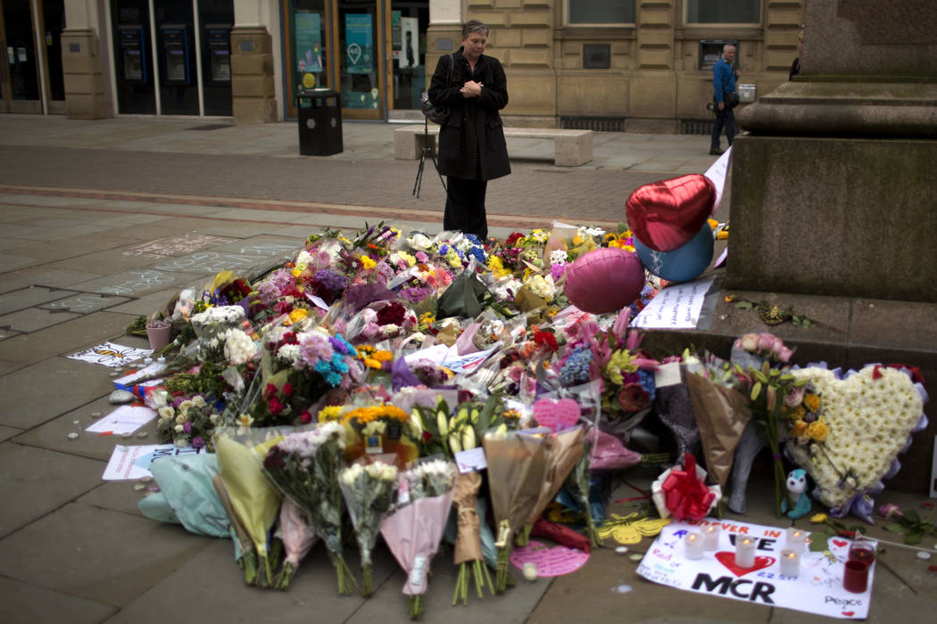 A woman stands next to flowers offered for the victims of a suicide attack at a concert by Ariana Grande that killed more than 20 people Monday night in central Manchester, Britain, Wednesday, May ...
