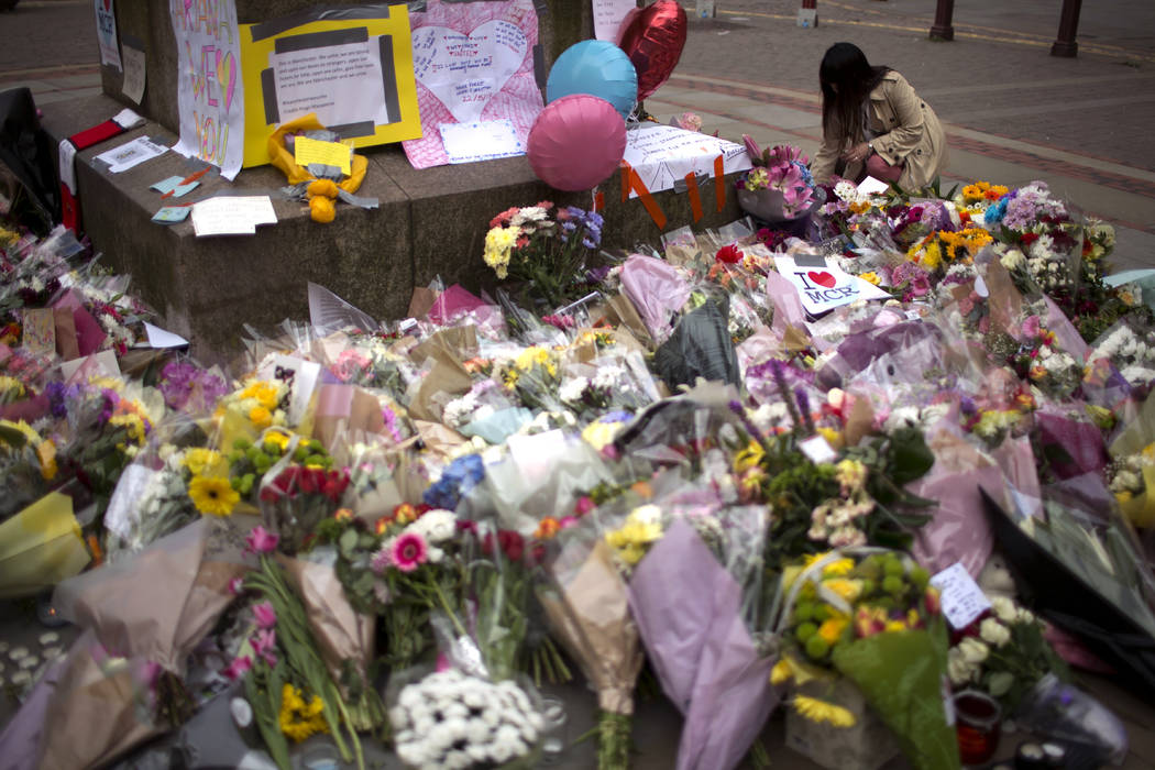 A woman places flowers at a memorial for the victims of a suicide attack at a concert by Ariana Grande that killed more than 20 people Monday night in central Manchester, Britain, Wednesday, May 2 ...