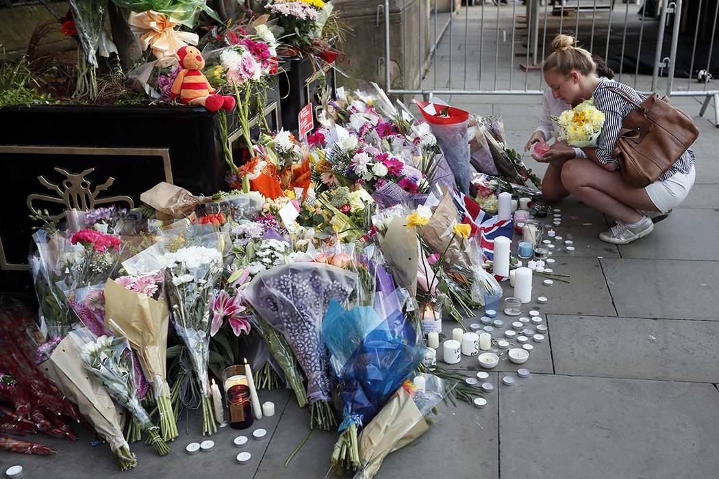 People lay flowers after a vigil in Albert Square, Manchester, England, Tuesday May 23, 2017, the day after the suicide attack at an Ariana Grande concert that left 22 people dead. (Kirsty Wiggles ...