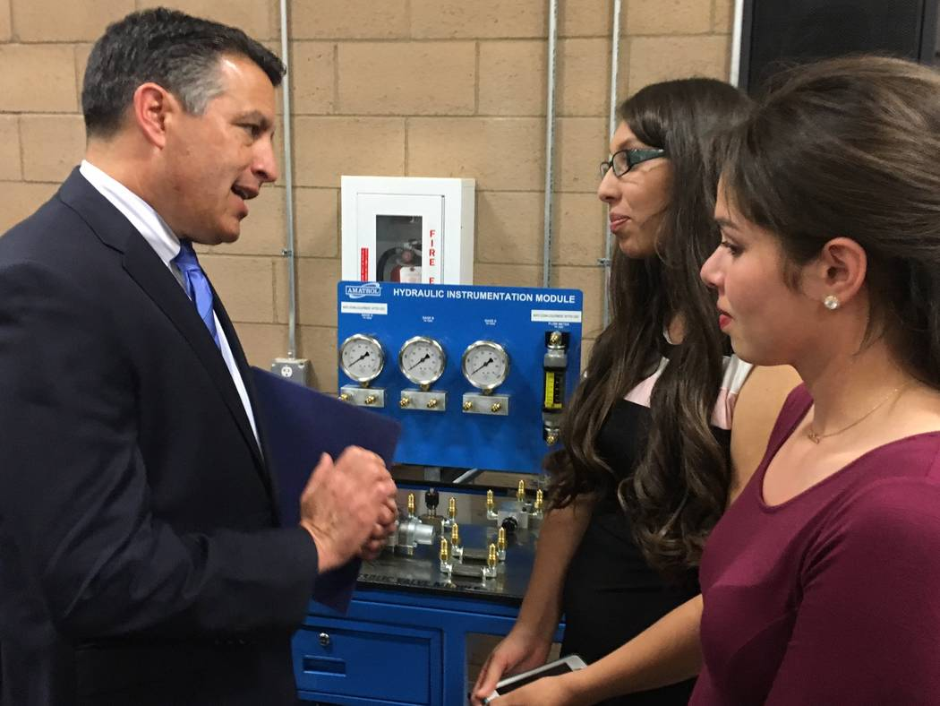 Gov. Brian Sandoval chats with Diana Gurrola,left, outgoing president of the Associated Students of Western Nevada College, and Tania Covarrubias, incoming president, before the bill signing Wedne ...