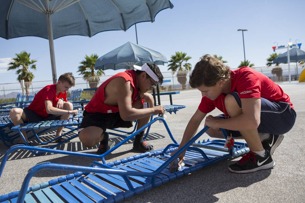 Ethan Lukow, left, Ivan Garcia, center, and Benjamin Bolmquist prep pool chairs at the Hollywood Aquatic Center's  outdoor pool on Thursday, May 25, 2017, in Las Vegas. Lifeguards cleaned the pool ...