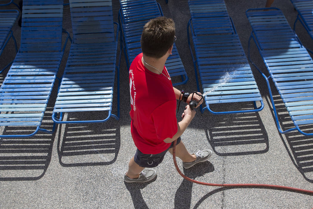 Reece Hartman sprays down pool chairs the outdoor pool at the Hollywood Aquatic Center's outdoor pool on Thursday, May 25, 2017, in Las Vegas. Lifeguards cleaned the pool and surrounding area of t ...