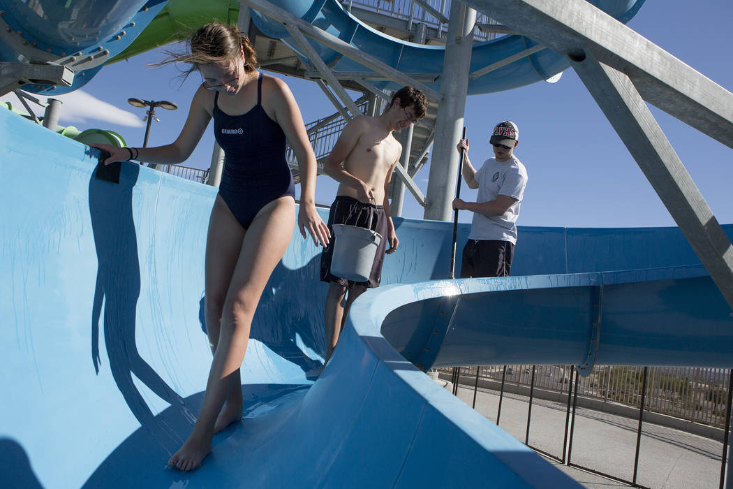 Cheyenne Brokaw, left, Tanner Thomas, center, and Jacob McQueen, right, work on cleaning a slide at the Hollywood Aquatic Center's outdoor pool on Thursday, May 25, 2017, in Las Vegas. Lifeguards  ...