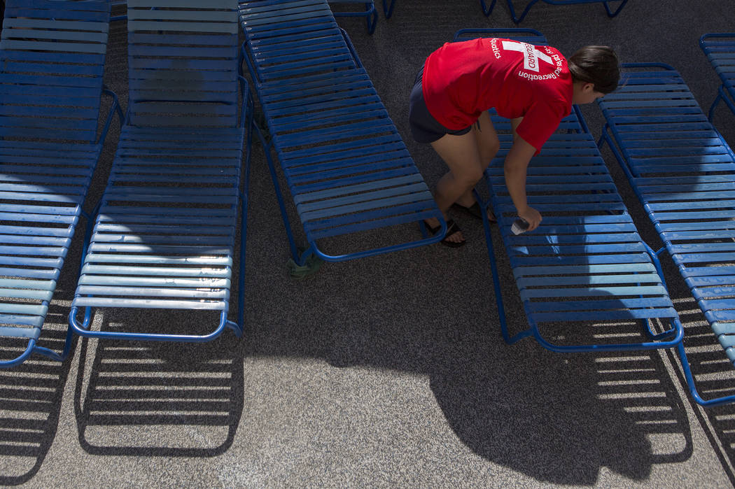 A lifeguard wipes down pool chairs at the Hollywood Aquatic Center's outdoor pool on Thursday, May 25, 2017, in Las Vegas. Lifeguards cleaned the pool and surrounding area of the pool for Memorial ...