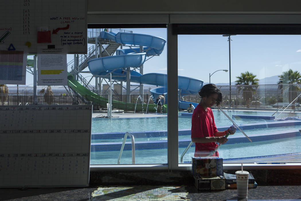 Adrian Razo helps clean windows at the Hollywood Aquatic Center's  outdoor pool on Thursday, May 25, 2017, in Las Vegas. Lifeguards cleaned the pool and surrounding area of the pool for Memorial D ...
