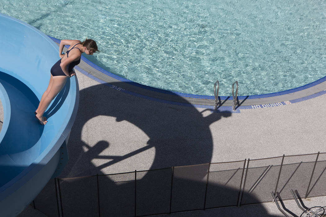 Cheyenne Brokaw looks over the edge of the slide while she works on cleaning it at the Hollywood Aquatic Center's  outdoor pool on Thursday, May 25, 2017, in Las Vegas. Lifeguards cleaned the pool ...