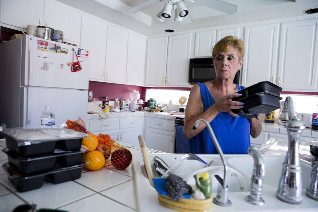 Olga Santiago puts away her Meals on Wheels delivery for her husband Rafael Santiago-Figueroa who suffers from multiple sclerosis at their home in Las Vegas, Thursday, May 25, 2017. Elizabeth Brum ...