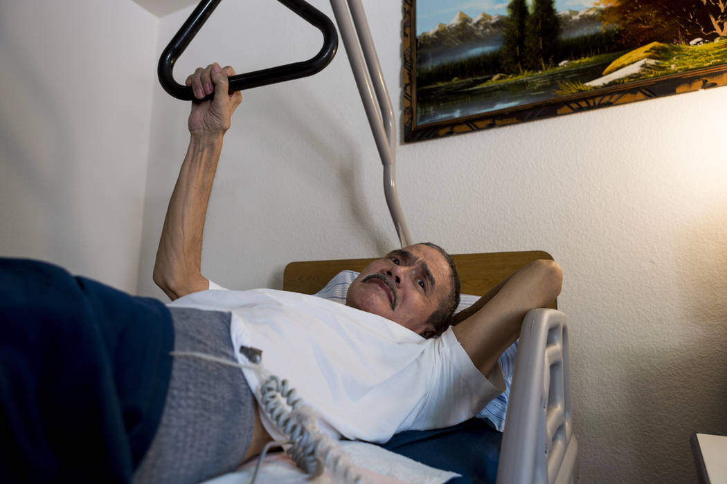 Rafael Santiago-Figueroa who suffers from multiple sclerosis watches television while his wife puts away his Meals on Wheels delivery in their home in Las Vegas, Thursday, May 25, 2017. Elizabeth  ...