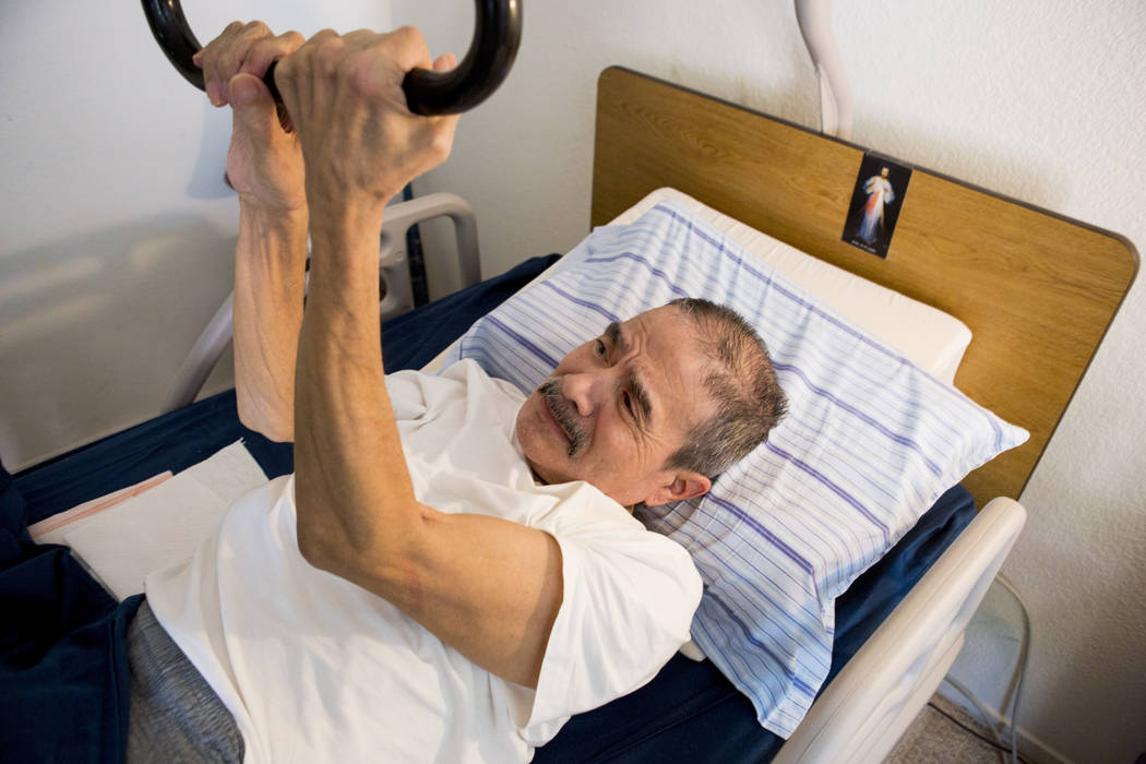 Rafael Santiago-Figueroa who suffers from multiple sclerosis readjusts in his bed while his wife puts away his Meals on Wheels delivery in their home in Las Vegas, Thursday, May 25, 2017. Elizabet ...