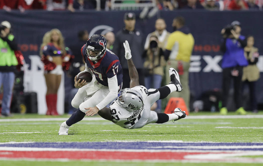 Houston Texans quarterback Brock Osweiler (17) scrambles for a first down against Oakland Raiders defensive end Mario Edwards (97) during the first half of an AFC Wild Card NFL football game Satur ...