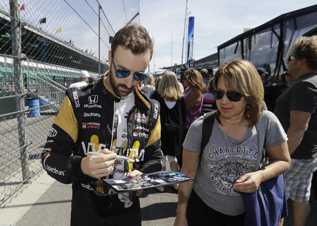 James Hinchcliffe, left, of Canada, gives autographs to fans following a practice for the Indianapolis 500 IndyCar auto race at Indianapolis Motor Speedway, Monday, May 22, 2017, in Indianapolis.  ...