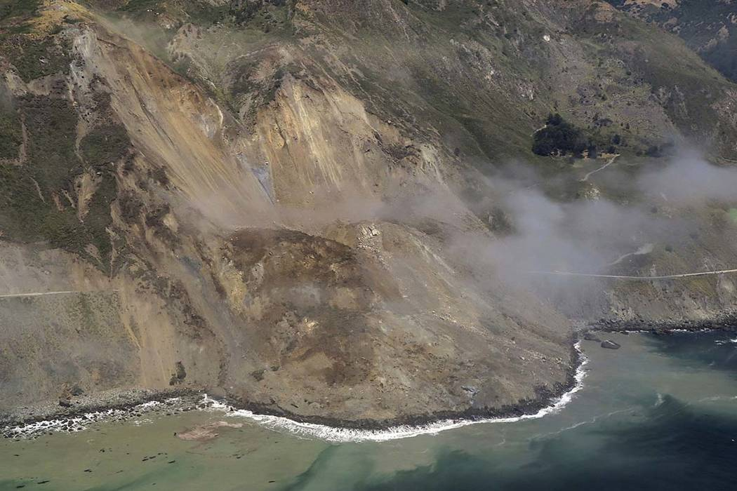In this aerial photo taken Monday, May 22, 2017, a massive landslide buried a portion of Highway 1  under a 40-foot layer of rock and dirt. A swath of the hillside gave way covering about one-thir ...