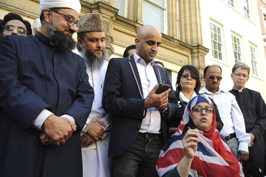 Religious leaders speak to crowds during a vigil at St Ann's square in central Manchester, England Wednesday May 24 2017. Britons will find armed troops at vital locations Wednesday after the offi ...