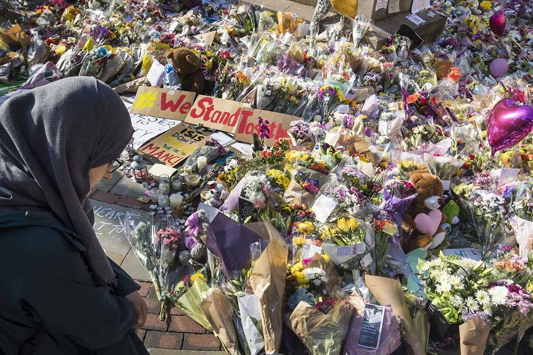 A woman looks at the floral tributes and messages left for the victims of the concert blast, during a vigil at St Ann's Square in central Manchester, England, Wednesday, May 24, 2017. Two more sus ...