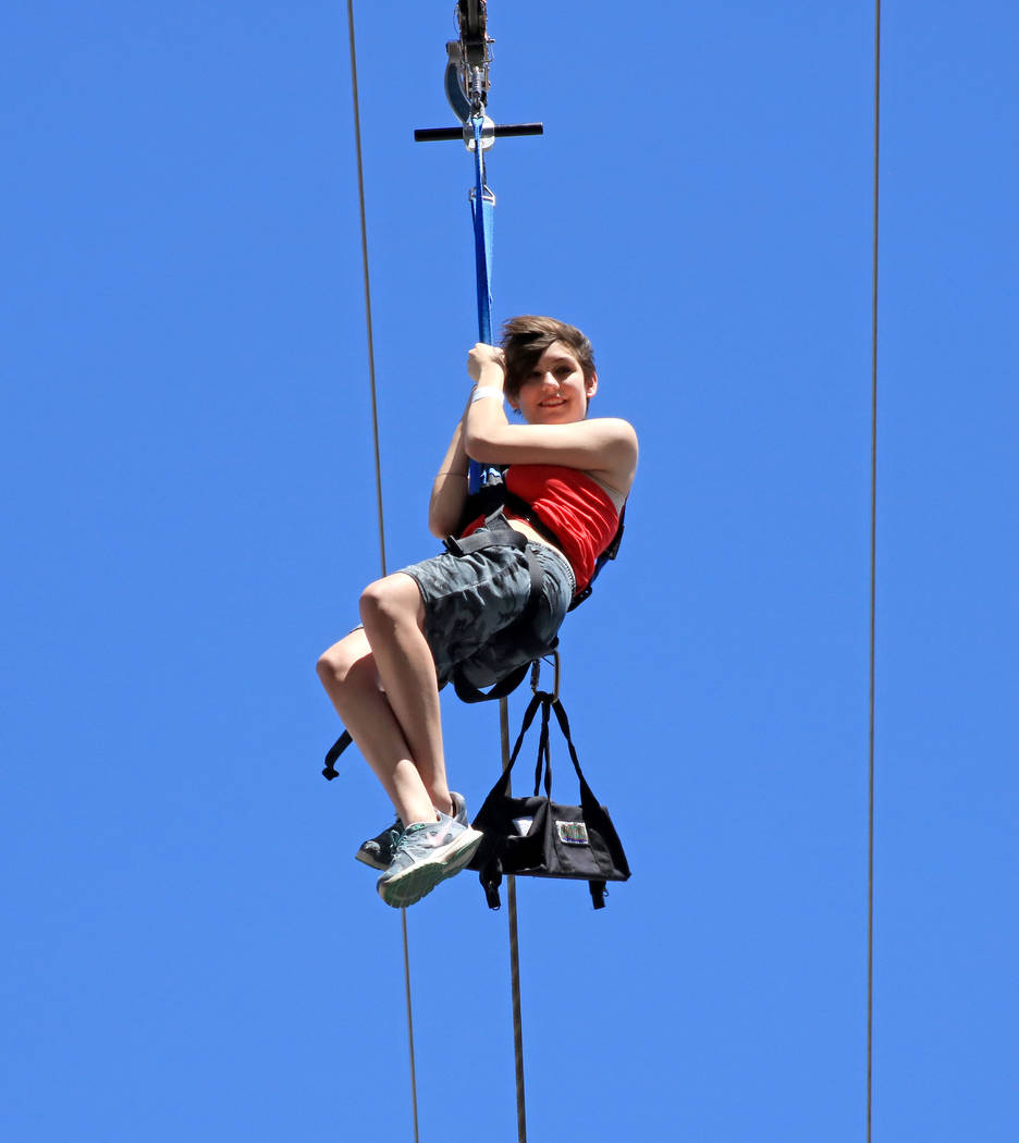 A tourist hangs on tight as they ride the SlotZilla Zip Line near the Fremont Street Experience, Thursday, May 25, 2017. Gabriella Benavidez Las Vegas Review-Journal @latina_ish