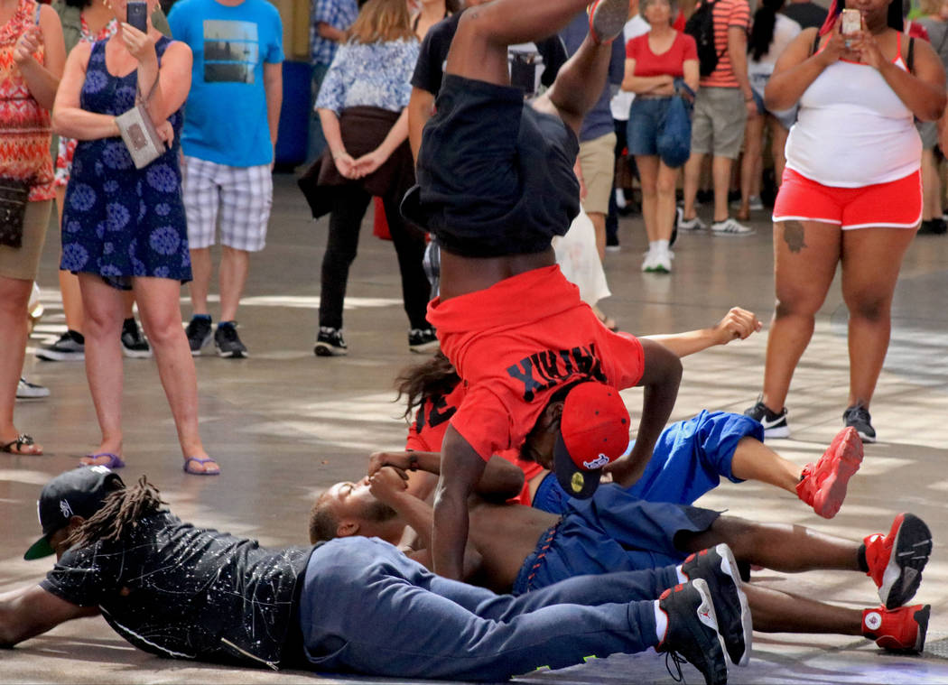 Patrick Bryant of Y.A.K. Crew, center, jumps over his fellow crew members as part of their routine at the Fremont Street Experience, Thursday, May 25, 2017. Gabriella Benavidez Las Vegas Review-Jo ...