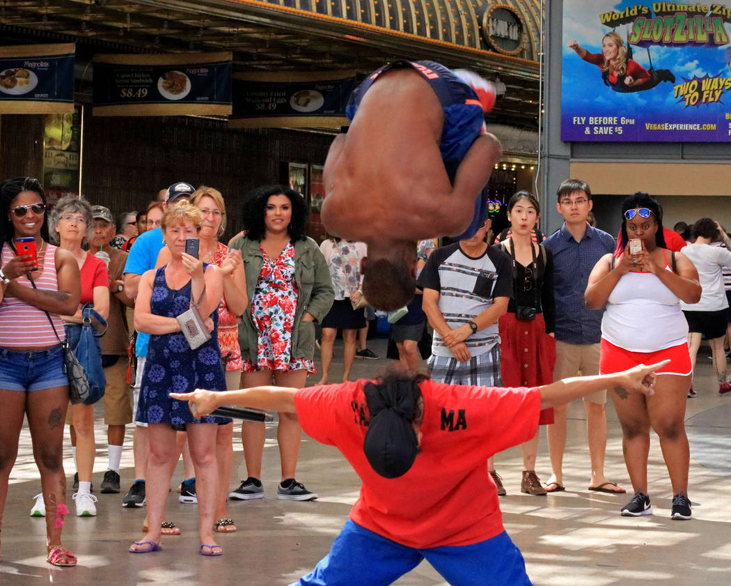 Cisco of Y.A.K. Crew, center, jumps over his fellow crew member, Jet, as part of their routine at the Fremont Street Experience, Thursday, May 25, 2017. Gabriella Benavidez Las Vegas Review-Journa ...