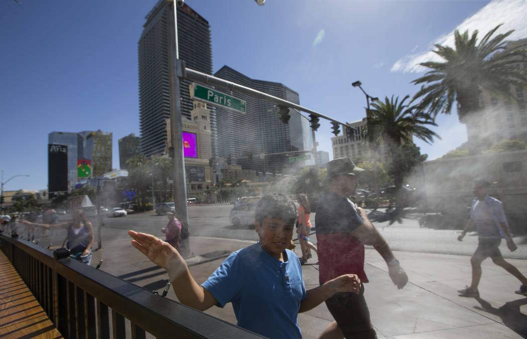 Pedestrians cool off on water misters along Las Vegas Boulevard in Las Vegas on Thursday, May 25, 2017. Richard Brian Las Vegas Review-Journal @vegasphotograph