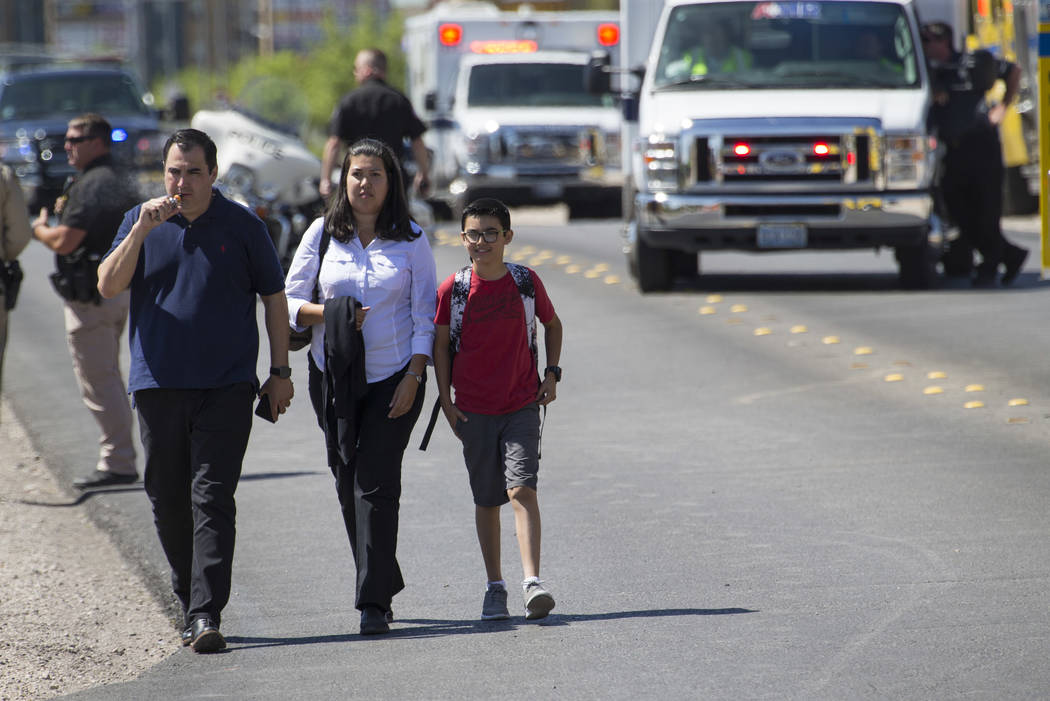 A family leaves the scene of an accident involving a Clark County school bus and SUV on S. Fort Apache Rd. near W. Patrick Ln. on Thursday, May 25, 2017. Richard Brian Las Vegas Review-Journal @ve ...