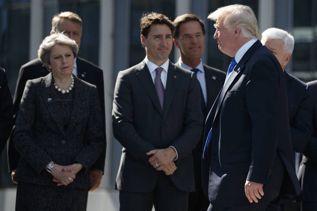 President Donald Trump walks past Canadian Prime Minister Justin Trudeau and British Prime Minister Theresa May after speaking during a ceremony to unveil artifacts from the World Trade Center and ...