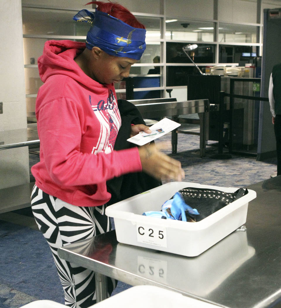 Alexis Boothe, of Chicago, drops her personal items in a bin in the TSA screening line at McCarran International Airport in Las Vegas, Dec. 3, 2013. More than $500,000 is found annually in loose c ...
