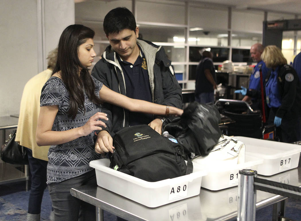 Ankita and Rohit Jain, left to right, of Denver, sort through their personal items in the TSA screening line at McCarran International Airport in Las Vegas, Dec. 3, 2013. More than $500,000 is fou ...