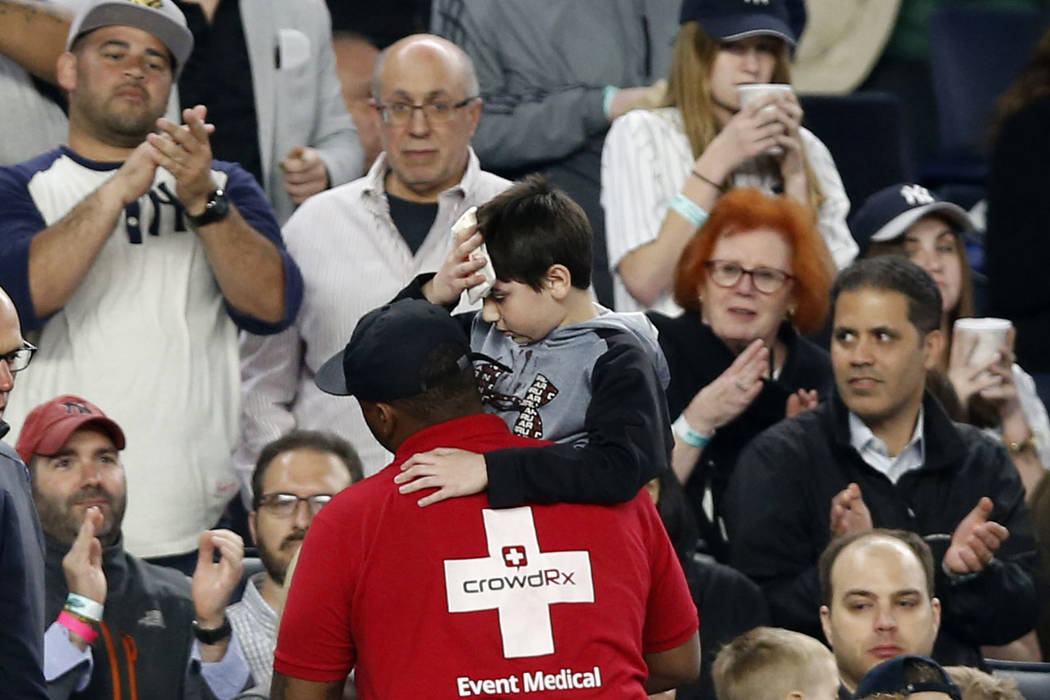 Fans applaud as a medical employee carries an injured youngster from the stands after the boy was hit in the head by a piece the Yankees's Chris Carter's bat that split during the seventh inning o ...