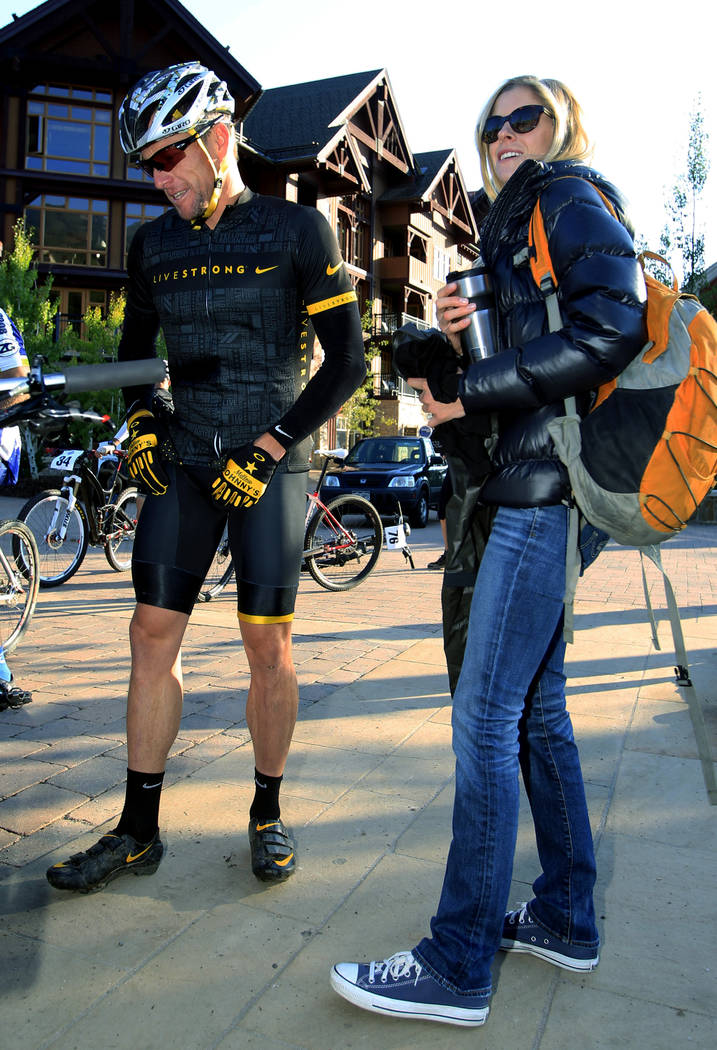 In this Aug. 25, 2012, file photo, Lance Armstrong stands with his girlfriend Anna Hansen as he prepares to take part in the Power of Four mountain bicycle race at the starting line in Snowmass Vi ...