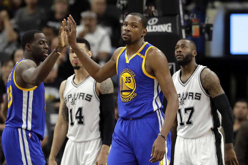 Golden State Warriors' Draymond Green (23) and Kevin Durant (35) celebrate a basket as San Antonio Spurs' Danny Green (14) and Jonathon Simmons (17) watch during the second half in Game 4 of the N ...