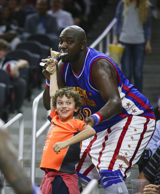 """Harlem Globetrotters' Nathaniel """"Big Easy"""" Lofton (52) gets a bite of a young fan's ice cream cone while performing at T-Mobile Arena in Las Vegas on Thursday, Feb. 9, 2017. (Cha ..."""