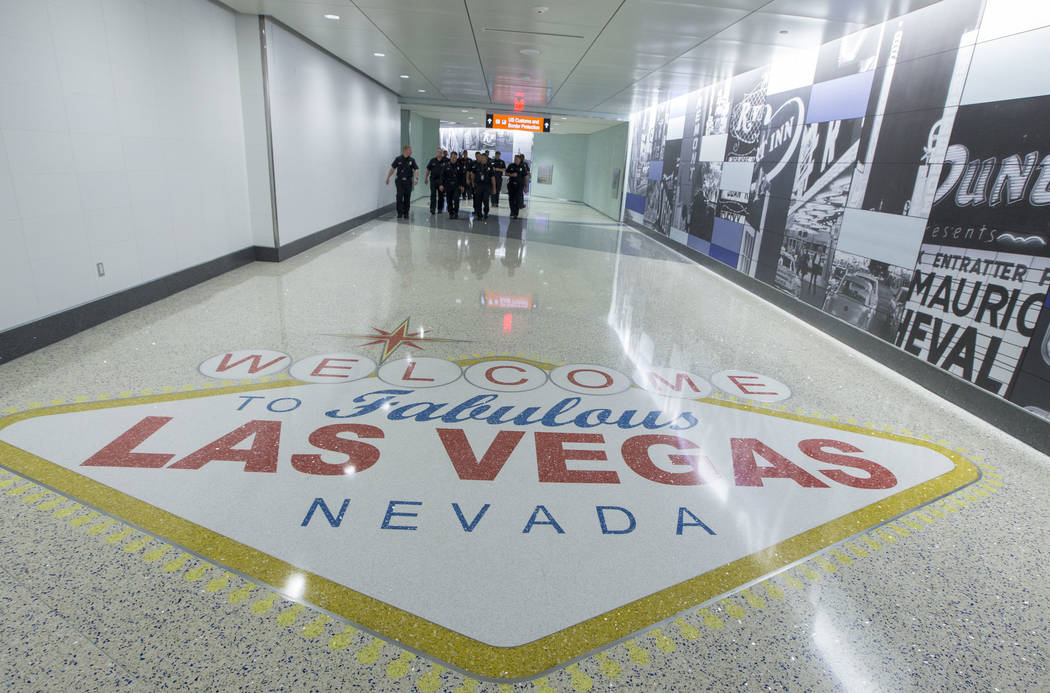 Clark County firefighters walk through the recently completed 995-foot-long corridor linking the D-Gate Concourse to the airport's U.S. Customs and Border Protection station in Terminal 3 a ...