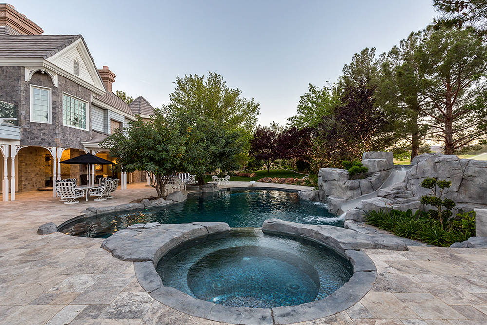 The backyard has a spa, pool and water slide. (The Tom Love Group)