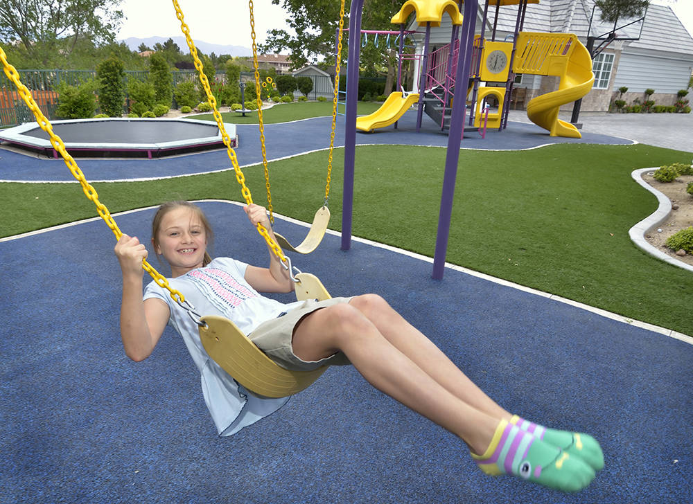 Siara Love plays on the swing in the playground in her backyard. (Bill Hughes/Las Vegas Business Press)