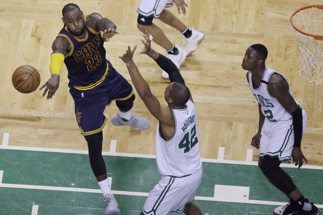 Cleveland Cavaliers forward LeBron James (23) passes the ball as Boston Celtics center Al Horford (42) and guard Terry Rozier, right, defend during the first half of Game 5 of the NBA basketball E ...