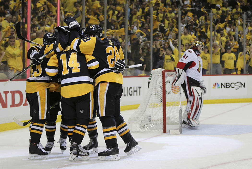 CORRECTS TO SECOND PERIOD - Pittsburgh Penguins left wing Chris Kunitz (14) celebrates with teammates after scoring a goal against the Ottawa Senators during the second period of Game 7 in the NHL ...