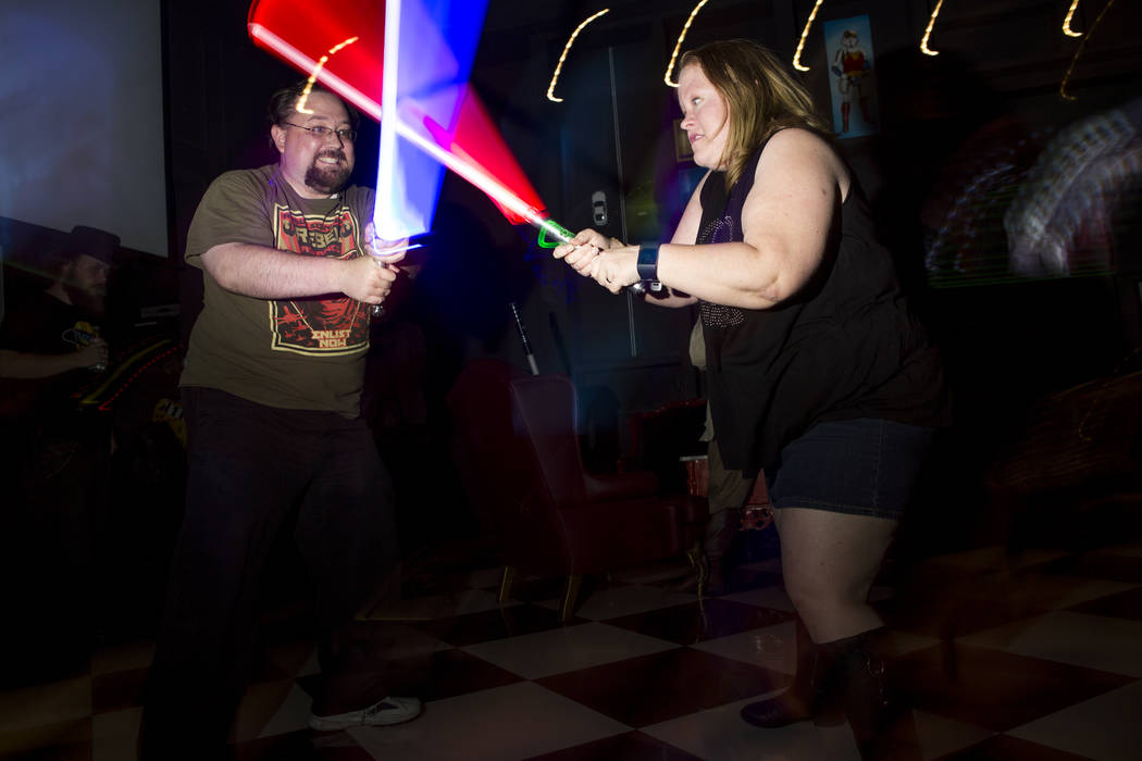 Gabriel Colbaugh, left, practices his lightsaber skills with Amanda Bond while celebrating the 40th anniversary of the release of Episode IV РA New Hope at the Millennium Fandom Bar in the A ...