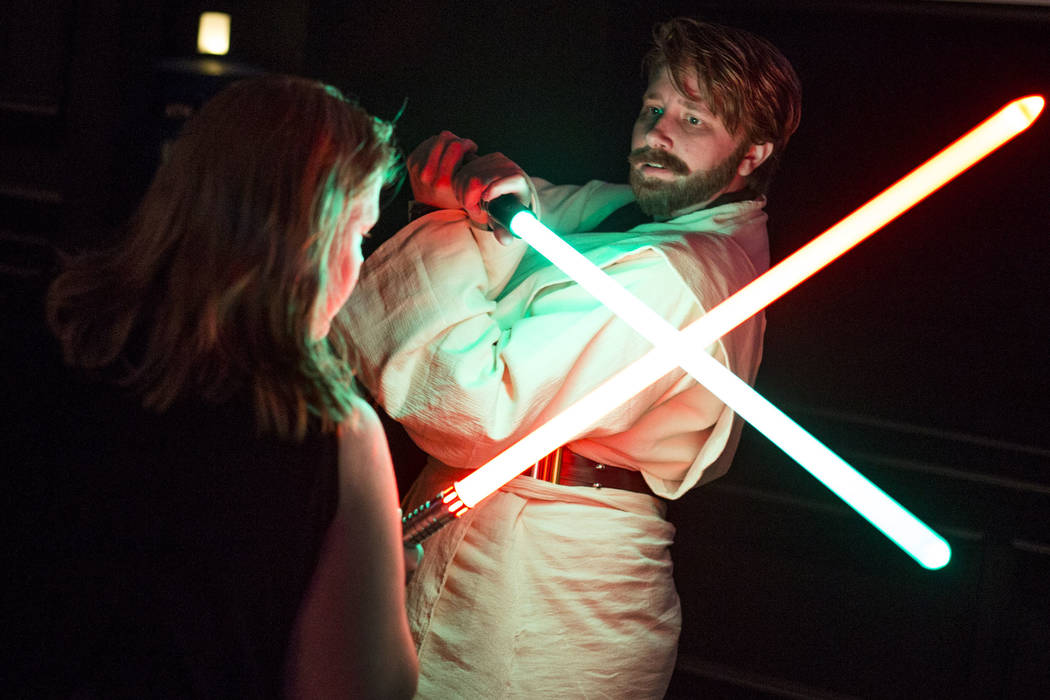 Amanda Bond, left, and Rebecca Zobell, dressed as Obi Wan Kenobi, practice their lightsaber skills as they celebrate the 40th anniversary of the release of Episode IV – A New Hope at the Mi ...