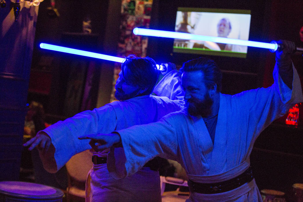 Rebecca Zobell, left, and Jack Stuart, both dressed as Obi Wan Kenobi, pose for their friends as they celebrate the 40th anniversary of the release of Episode IV РA New Hope at the Millenniu ...