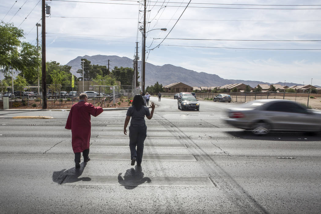 A car passes as Officer Robert Mayer of the Clark County School District Police and Shae Moore, an EMT with Community Ambulance, cross Nellis Boulevard in Las Vegas on Tuesday, May 30, 2017. Multi ...