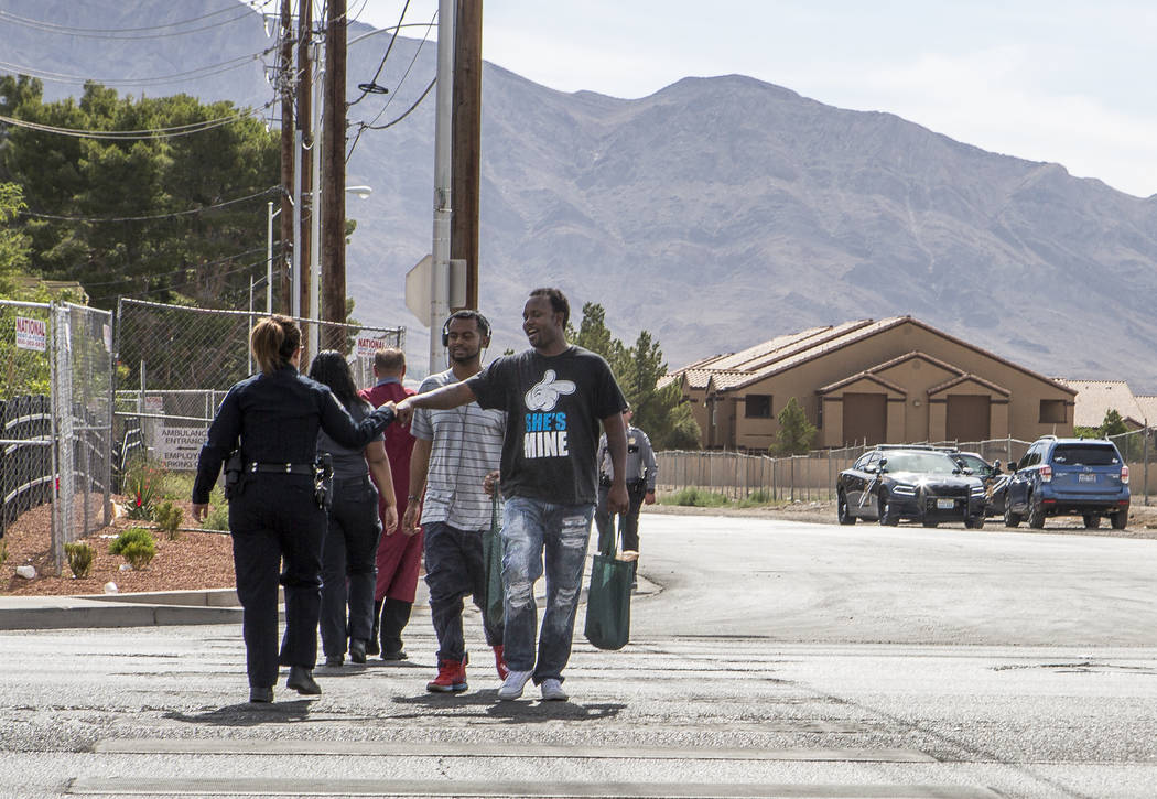 """A pedestrian fist bumps a police officer while crossing Nellis Boulevard in Las Vegas on Tuesday, May 30, 2017. Multiple police departments joined together for an event, """"Grad in the Cros ..."""