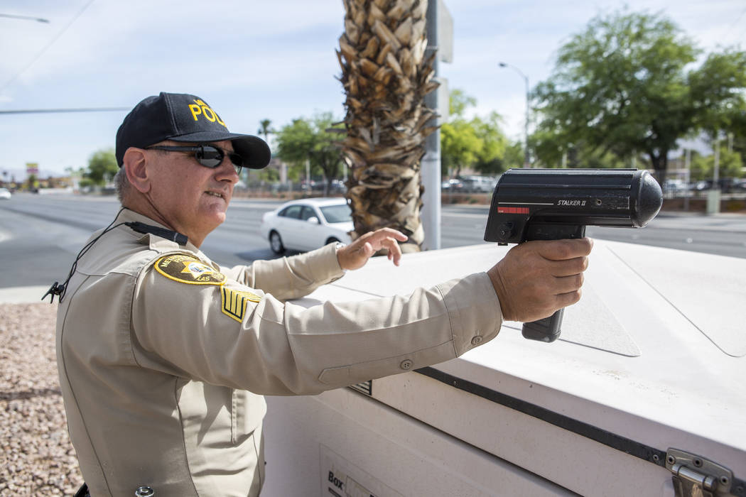 Sgt.Peter Kisfalvi of the Las Vegas Metropolitan Police uses a radar gun to find speeding motorists at the intersection of Nellis Boulevard and Cedar Avenue on Tuesday, May 30, 2017. Multiple poli ...