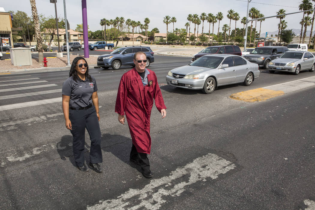 Officer Robert Mayer of the Clark County School District Police and Shae Moore, an EMT with Community Ambulance, cross Nellis Boulevard in Las Vegas on Tuesday, May 30, 2017. Multiple police depar ...