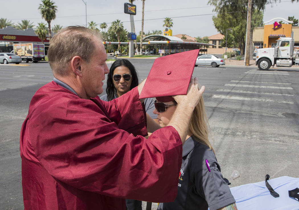 Officer Robert Mayer of the Clark County School District Police puts a graduation cap on Melanie Bangle, a paramedic with Community Ambulance, at the intersection of Nellis Boulevard and Cedar Ave ...