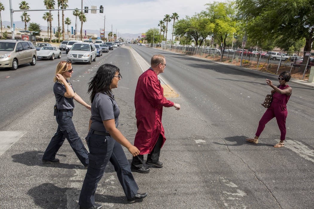 Officer Robert Mayer of the Clark County School District Police, Shae Moore, center, and Melanie Bangle with Community Ambulance, wave to a pedestrian as they cross Nellis Boulevard in Las Vegas o ...