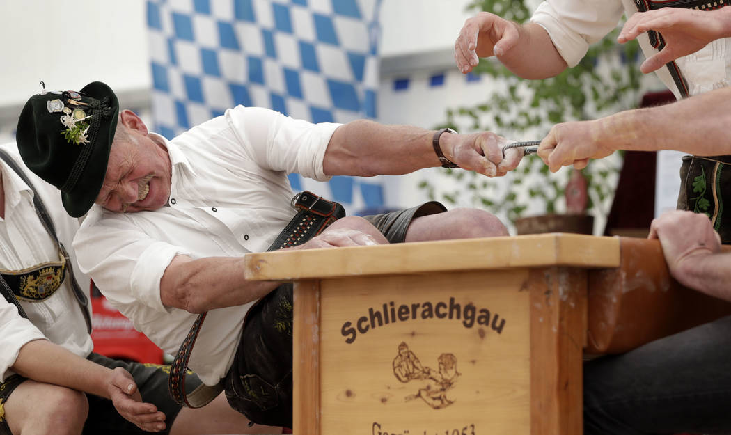 Georg Schoettl tries to pull his opponent over the table at the 40th Alpine Country Championships in Fingerhakeln_finger wrestling_ in Woernsmuehl, Germany, Thursday, May 25, 2017. Competitors bat ...